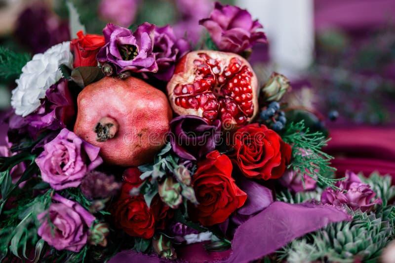 Heiratender asymetrischer stilvoller Blumenstrauß mit roten Rosen und Granatapfel stockbilder