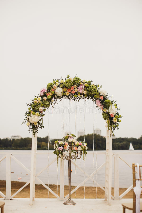 Heiratender Blumenbogen auf dem Strand stockfotos