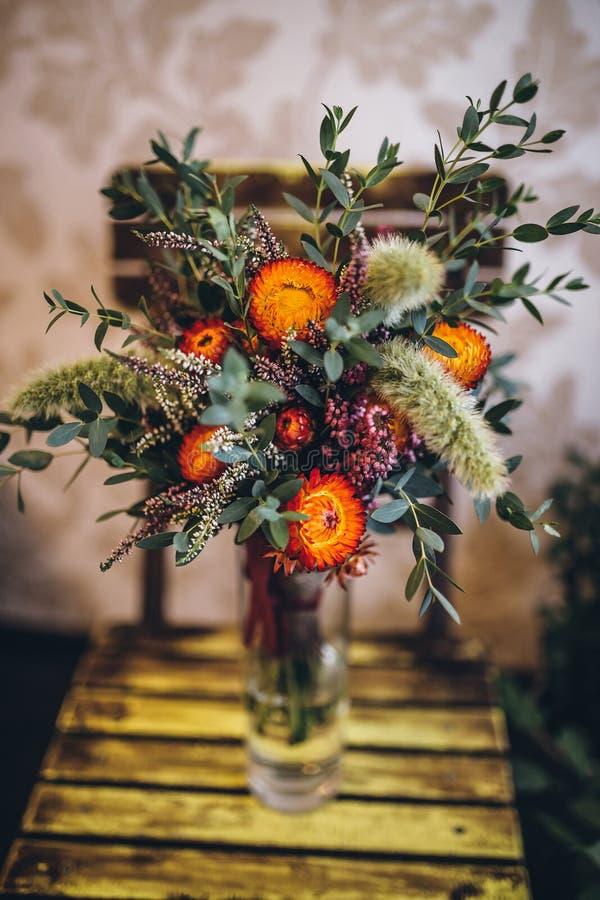 Heiratender rustikaler Blumenstrauß von trockenen Blumen auf Stuhl stockfotografie