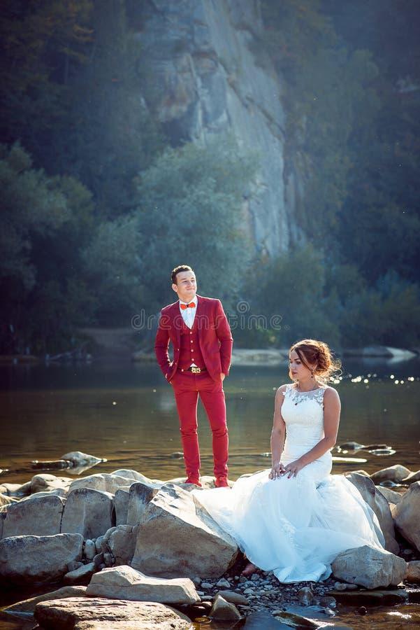 Heiratendes vertikales Porträt des reizend Jungvermähltens verbinden das Stillstehen nahe dem Fluss Die rote Hauptbraut sitzt auf lizenzfreies stockbild