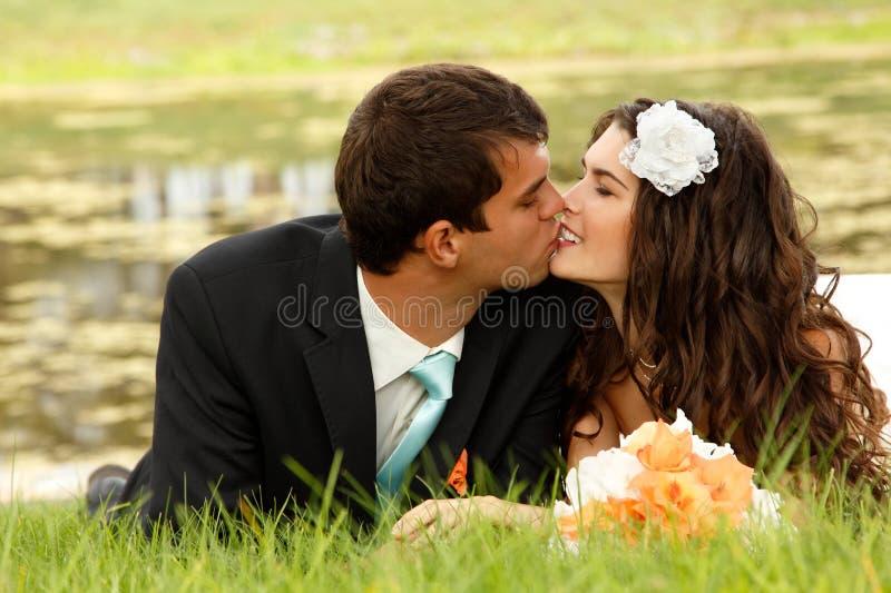 Heirats, junge Braut und Bräutigam in der Liebe, die auf grünem Gras, Gleichheit liegt lizenzfreie stockfotos