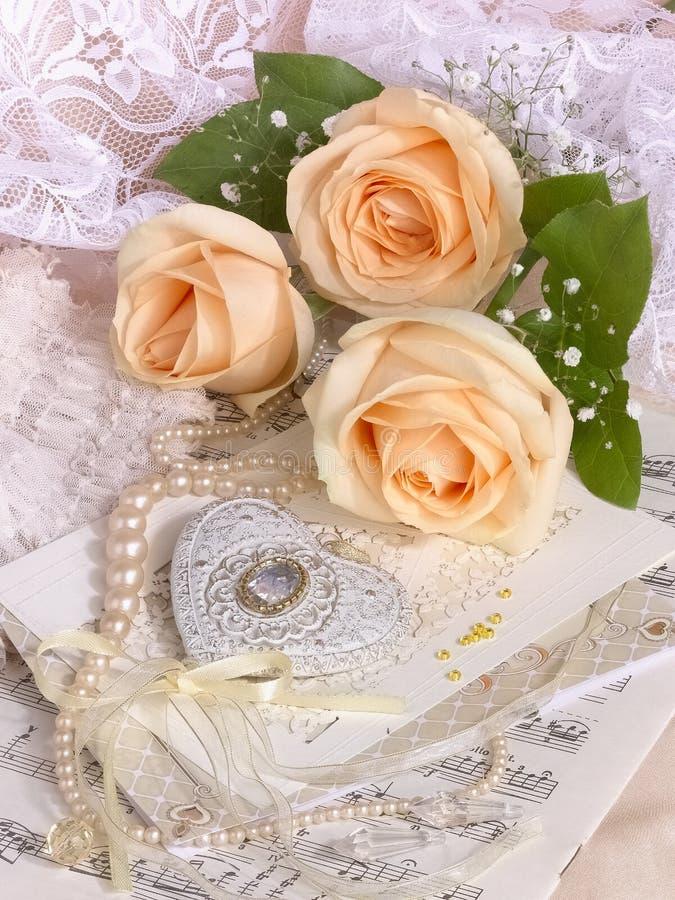Heiratsbild mit Teerosen und Perlenhalskette stockfotos