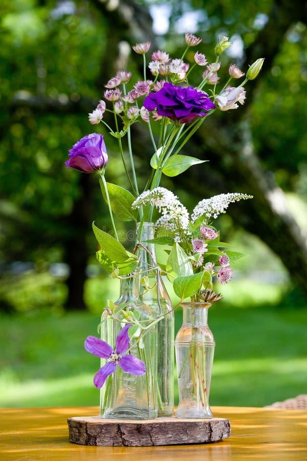 Heiratsblumenanordnungs-Reihe Blumenstrauß von Blumen für ein Heiratsereignis in den klaren Flaschen stockbild