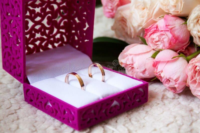 Heiratsblumenstrauß und Ringe im Kasten auf einem Luxussofa stockbild