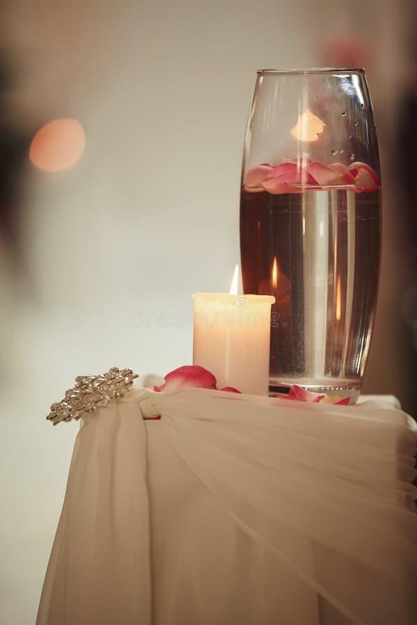 Heiratsdekoration ein Kerze und ein Vase mit Wasser auf einer weißen Tabelle Flaschen mit Wasser und einer Schwimmkerze lizenzfreies stockbild