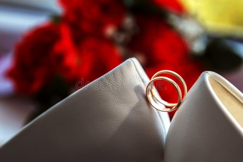 Heiratshintergrund mit Ringen, Blumenstrauß und weißer Schuhbrücke stockfotografie