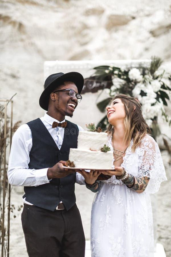Heiratshippiepaare auf der Natur die Braut und der Br?utigam mit rustikalem Kuchen an der Hochzeit lizenzfreies stockbild