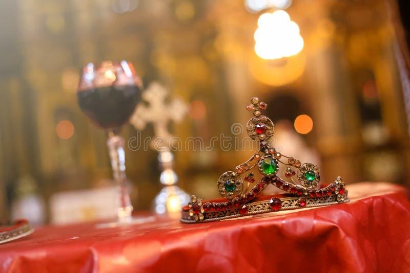 Heiratskrone und unscharfes Glas der Rebe und des Kreuzes im Hintergrund Orthodoxe Zusätze der kirchlichen Hochzeit stockbilder