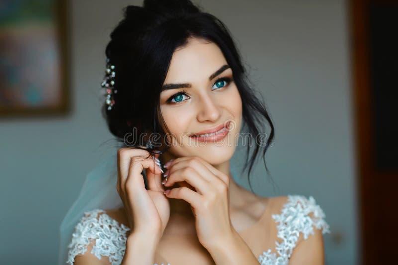 Heiratsohrringe auf einer weiblichen Hand, nimmt sie die Ohrringe, die Brautgebühren, Morgenbraut, weißes Kleid, Abnutzungsohrrin lizenzfreie stockfotografie