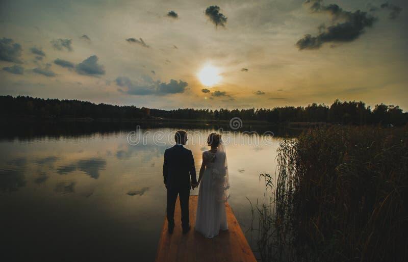 Heiratspaar steht und betrachtet einander im Sonnenuntergang D?mmerung ?ber dem See Wei?es Kleid und Brautschleier mit Spitze H?n stockbild