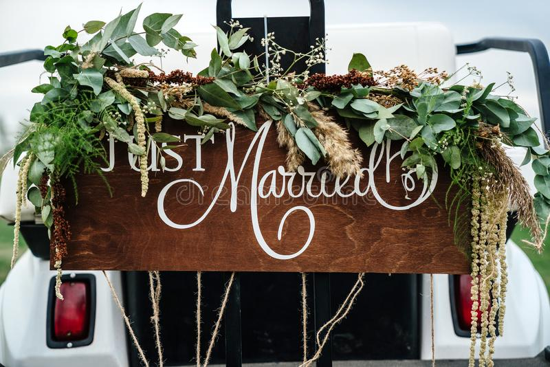 Heiratsschild gerade geheiratet in einem Golfwagen geschmückt mit Blumen auf einem Golfplatz stockfotografie