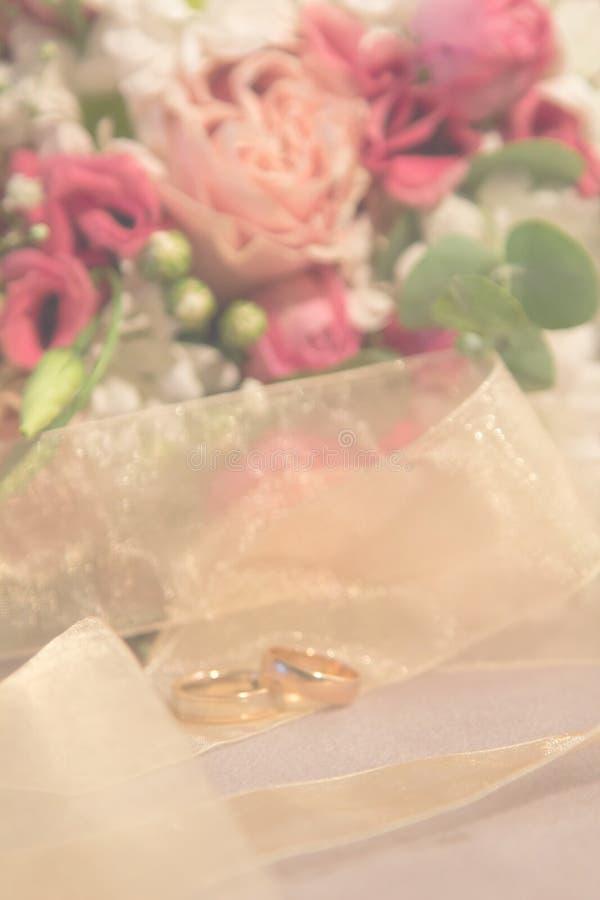 Heiratsunscharfer Hintergrund: Rosen-Blumenstraußvertikale der Eheringe natürliche lizenzfreie stockfotos