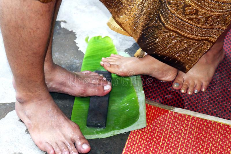 Heiratswaschende Füße der paare und Fuß auf einem Schleifstein und Bananenblättern für gutes Glück des Glaubens nehmen, ursprüngl stockbilder
