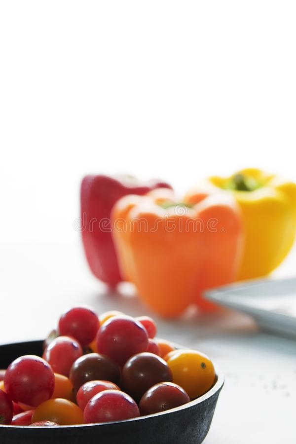 Heirloom cherry tomatoes with out of focus bell peppers in background. High key. Negative space stock photo