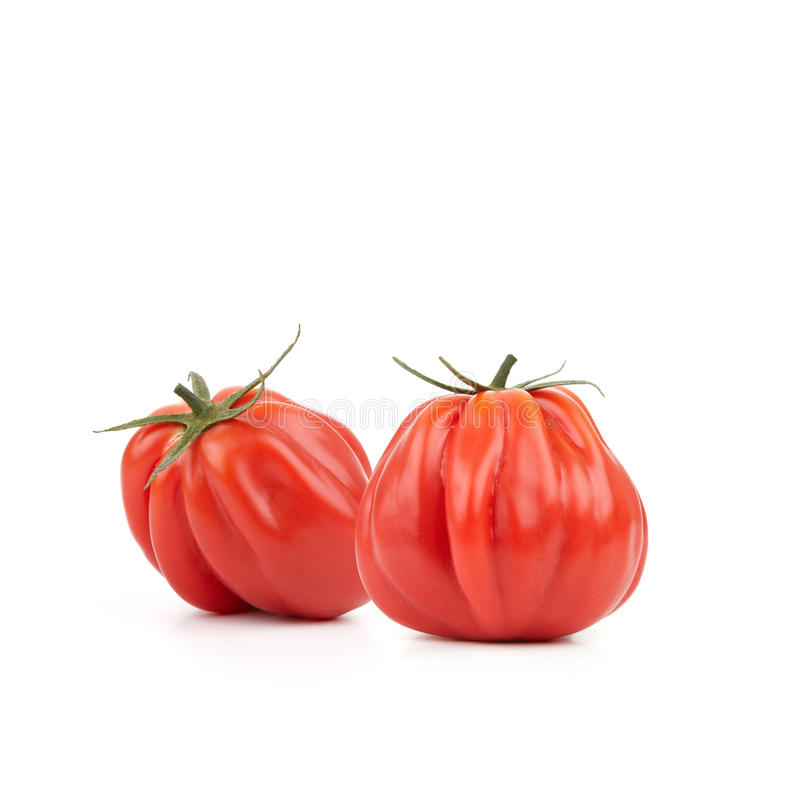 Heirloom Tomatoes. Two fresh and tasty looking Heirloom Tomatoes on white background royalty free stock photos