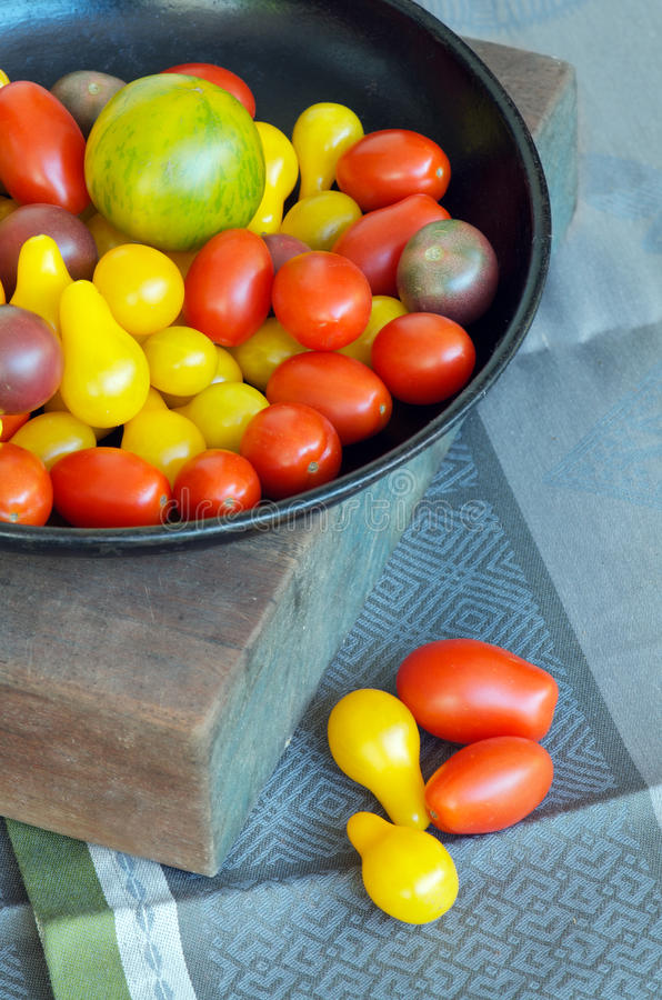 Heirloom tomatoes. Plate of tasty colourful heirloom tomatoes, including yellow pear and green zebra tomato cultivar royalty free stock photography
