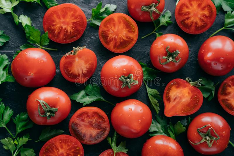 Heirloom tomatoes with green parsley for making vegetable salad. Juicy vegetables on dark background. Harvesting and food vitamins stock photos