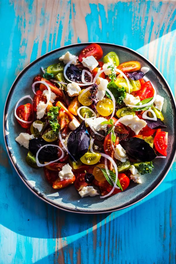 Heirloom tomatoes salad with cheese and basil royalty free stock photography