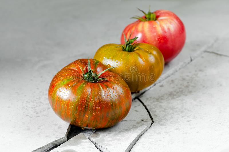 Heirloom tomatoes. Three tomatoes of different colors on a gray concrete table with a crack royalty free stock photo