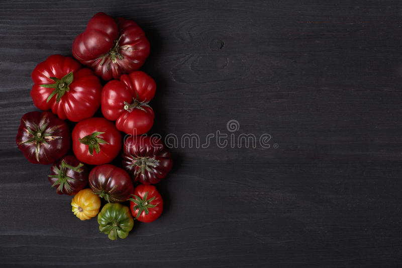 Heirloom tomatoes on wooden black board. Different heirloom tomatoes on wooden black board as design background with copy space stock images