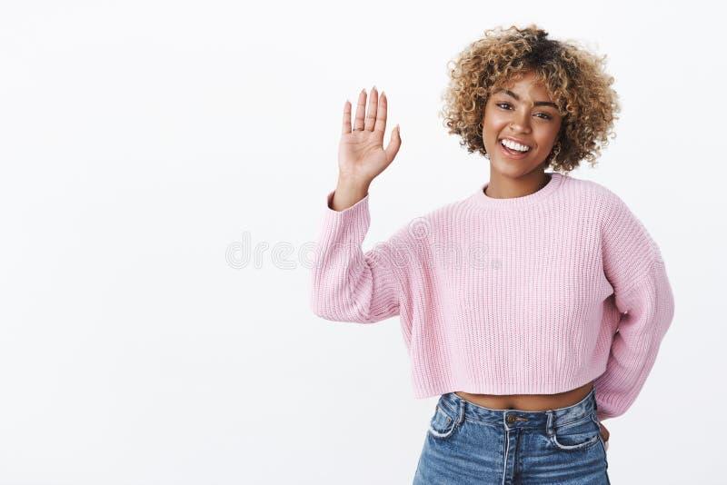 Hej daje ja wysokości pięć Życzliwa, radosna charyzmatyczna dziewczyna z blond afro ostrzyżeniem w zima puloweru eleganckim  obraz royalty free