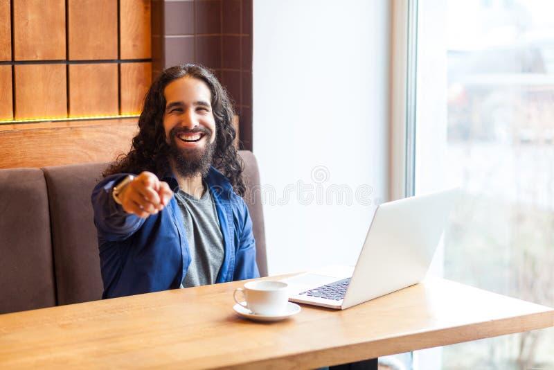 Hej dig! Stående av den lyckliga stiliga unga vuxna manfreelanceren i tillfällig stil som sitter i kafé och att peka fingret som  arkivbilder
