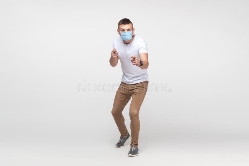 Hej. Full längd för en allvarlig ung man i vit skjorta med operationsmasken stående, som ser och pekar på arkivfoton