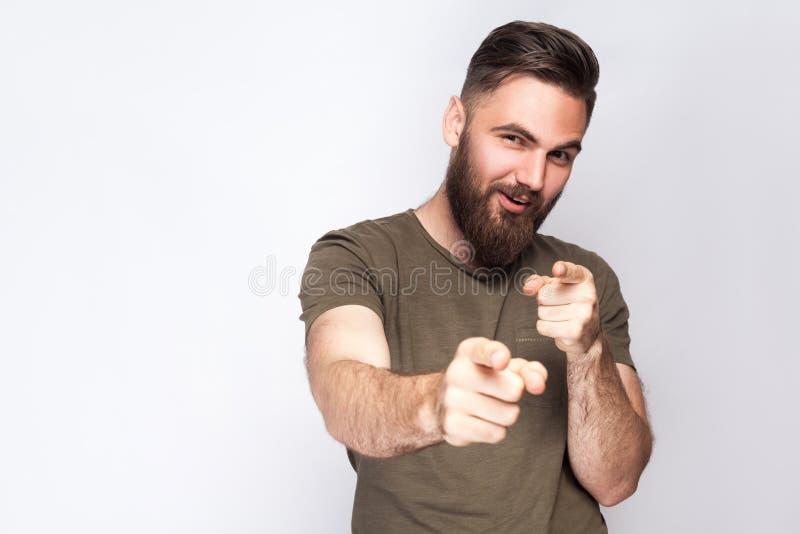 Hej ty! Portret szczęśliwy brodaty mężczyzna z ciemnozieloną t koszula przeciw światłu - szary tło zdjęcie royalty free
