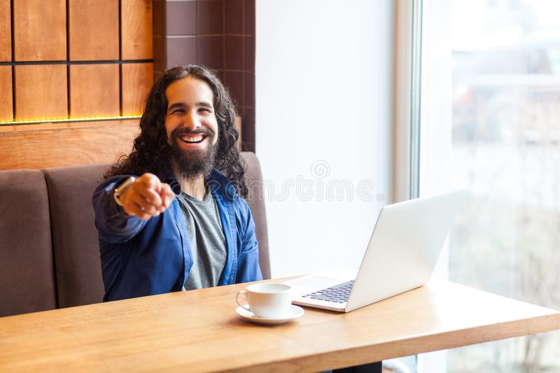 Hej ty! Portret szczęśliwy przystojny młody dorosły mężczyzny freelancer w przypadkowego stylu obsiadaniu w kawiarni, wskazujący  obrazy stock