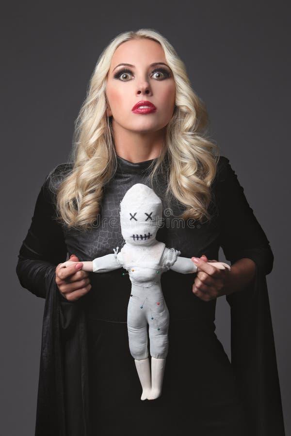 Heks die een voodoopop houden Kostuum voor Halloween-Partij Blonde heks royalty-vrije stock afbeeldingen