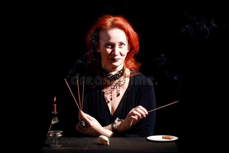 Heks met tovenaarskaars Fijne emotionele roodharigeheks met magische decoratie en levende uitdrukkingen stock afbeelding