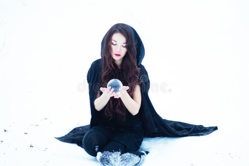 Heks in zwarte mantel met magiс bal stock foto