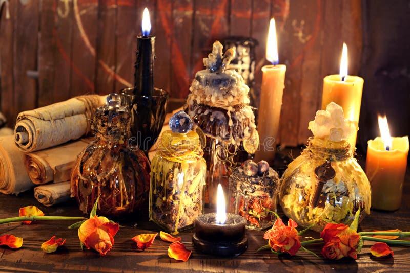 Heksenflessen, zwarte kaarsen en rozen agains planken met pentagram stock foto's