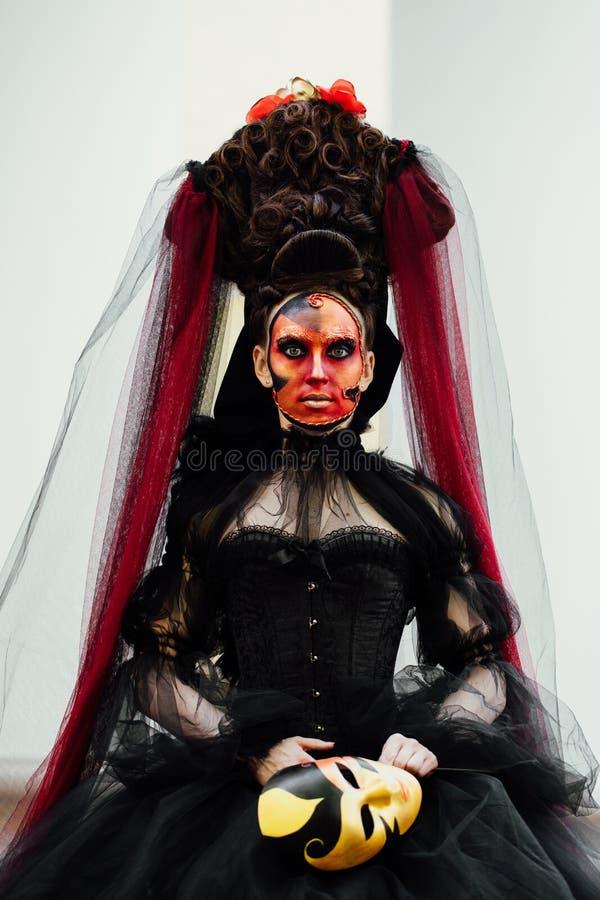Heksenportret in zwarte uitstekende kleding De vrouwenweduwe met rode kunst maakt Halloween goed stock fotografie