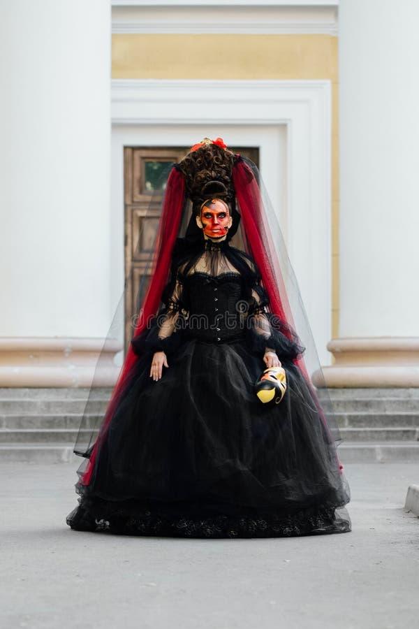 Heksenportret in zwarte uitstekende kleding De vrouwenweduwe met rode kunst maakt Halloween goed stock foto's