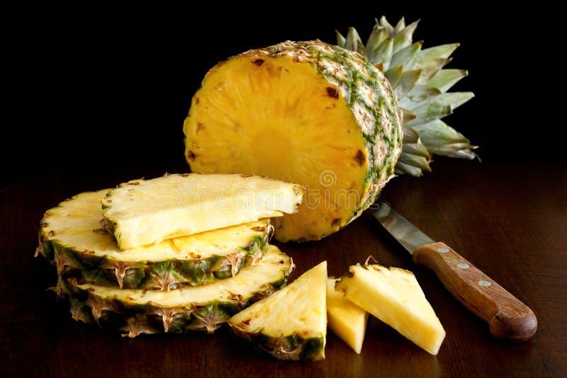 Hel ananas klippte upp med stycken och baktalar isolaten royaltyfri foto