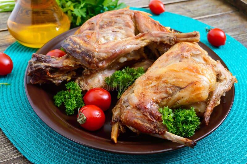Hel bakad kanin med gräsplaner och tomater på en platta Smakligt diet-kött royaltyfria foton