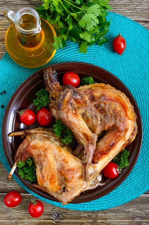 Hel bakad kanin med gräsplaner och tomater på en platta Smakligt diet-kött royaltyfria bilder