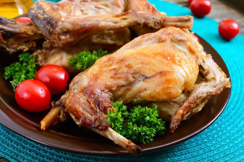 Hel bakad kanin med gräsplaner och tomater på en platta Smakligt diet-kött royaltyfri bild