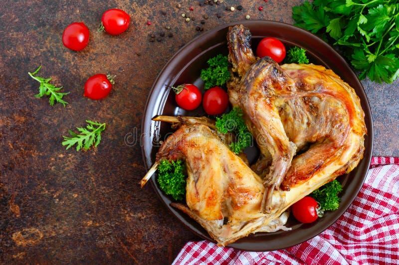 Hel bakad kanin med gräsplaner och tomater på en platta Smakligt diet-kött B?sta sikt, lekmanna- l?genhet royaltyfri foto