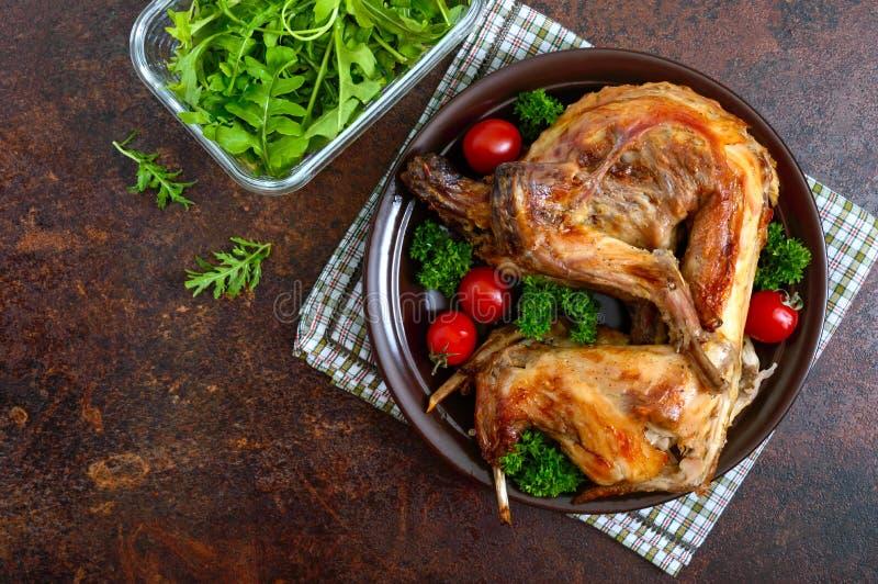 Hel bakad kanin med gräsplaner och tomater på en platta Smakligt diet-kött B?sta sikt, lekmanna- l?genhet royaltyfri bild