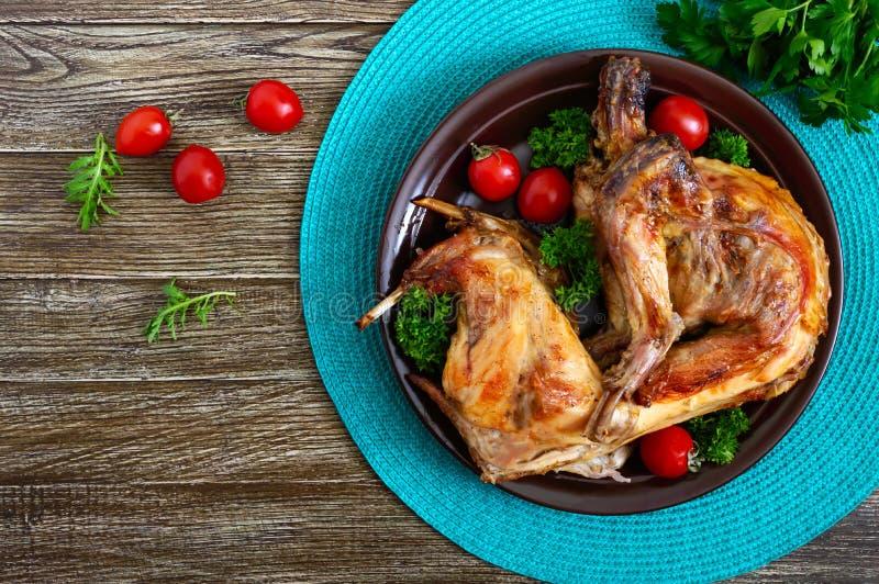 Hel bakad kanin med gräsplaner och tomater på en platta Smakligt diet-kött B?sta sikt, lekmanna- l?genhet arkivfoto