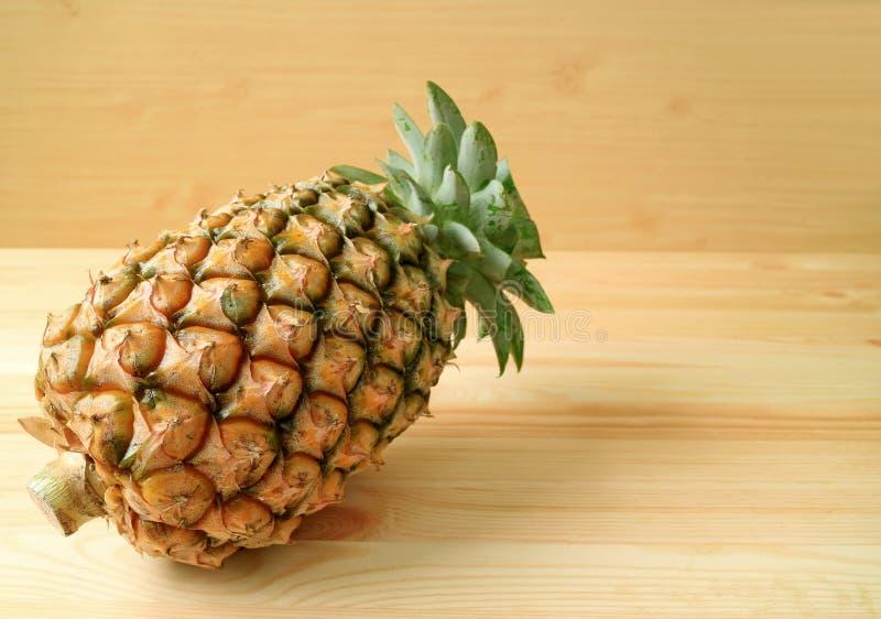 Hel frukt av ny mogen ananas på en trätabell, med fritt utrymme för design royaltyfri foto