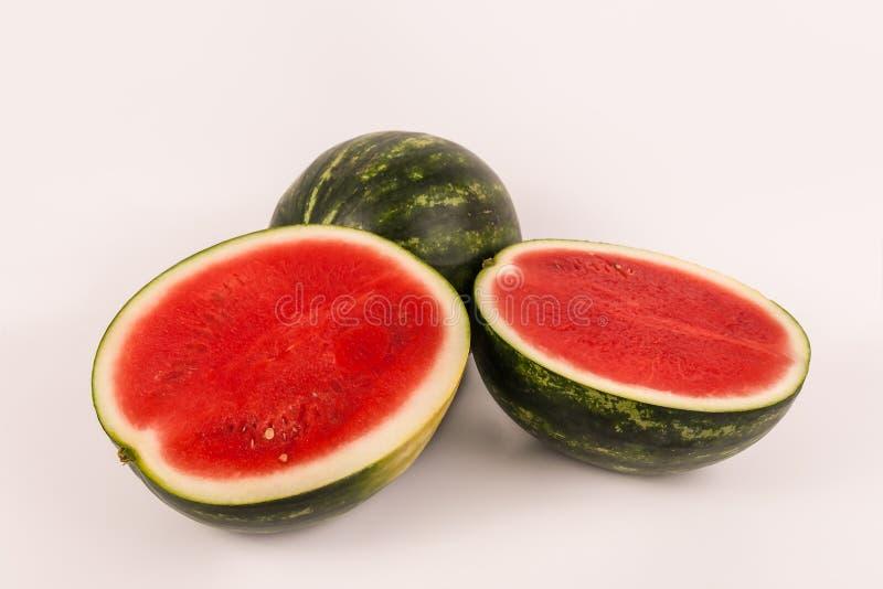 Hel man och två halverade röda kärnfria organiska vattenmelon arkivbilder