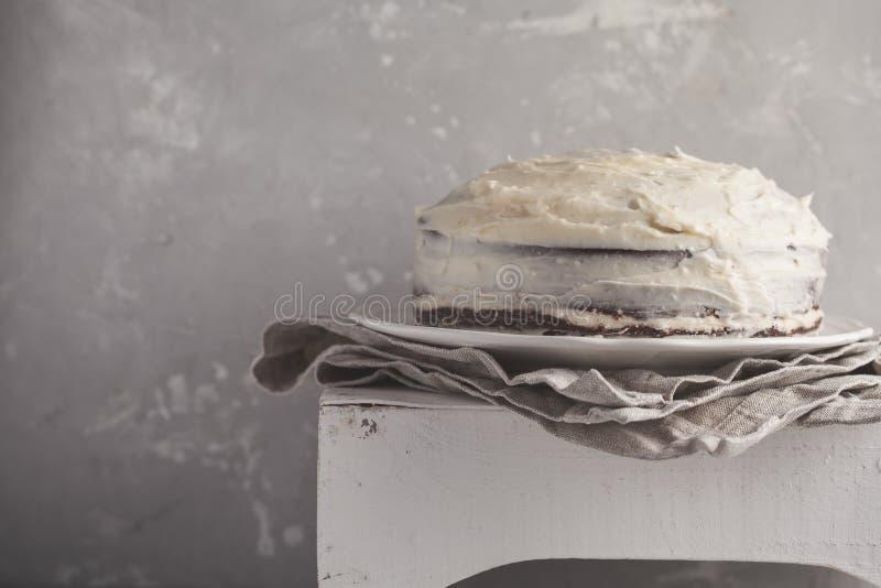 Hel morotkaka med vitkräm på en grå bakgrund Festi royaltyfri bild