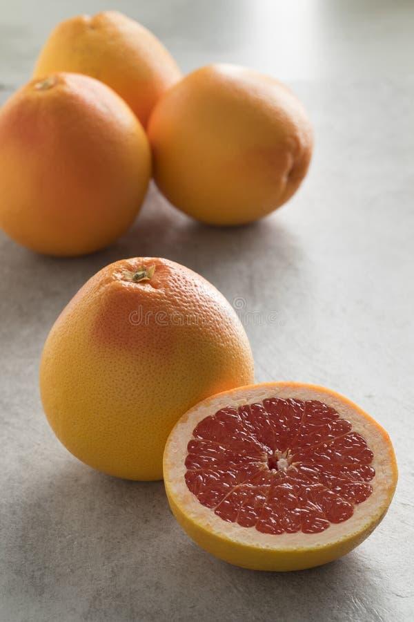 Hel och halverad röd grapefrukt royaltyfri fotografi
