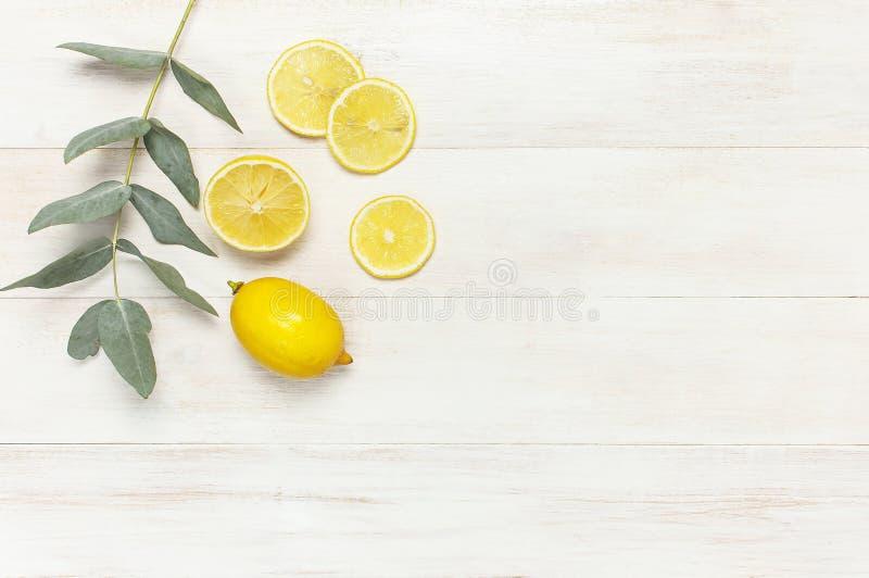 Hel och skivad ny citron, eukalyptussidor på vit träbakgrund Lekmanna- lägenhet, bästa sikt, kopieringsutrymme Minsta fruktbegrep royaltyfria foton