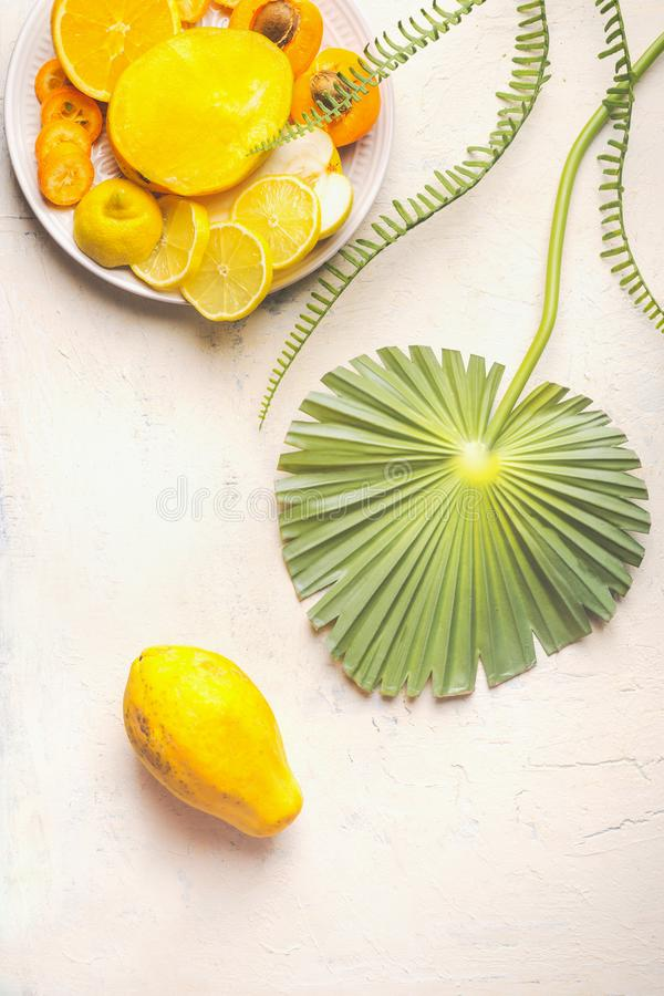 Hel papayafrukt på den vita tabellen med tropiska sidor och plattan med gula skivade frukter, bästa sikt Sommarmat ?ta som ?r sun royaltyfria bilder
