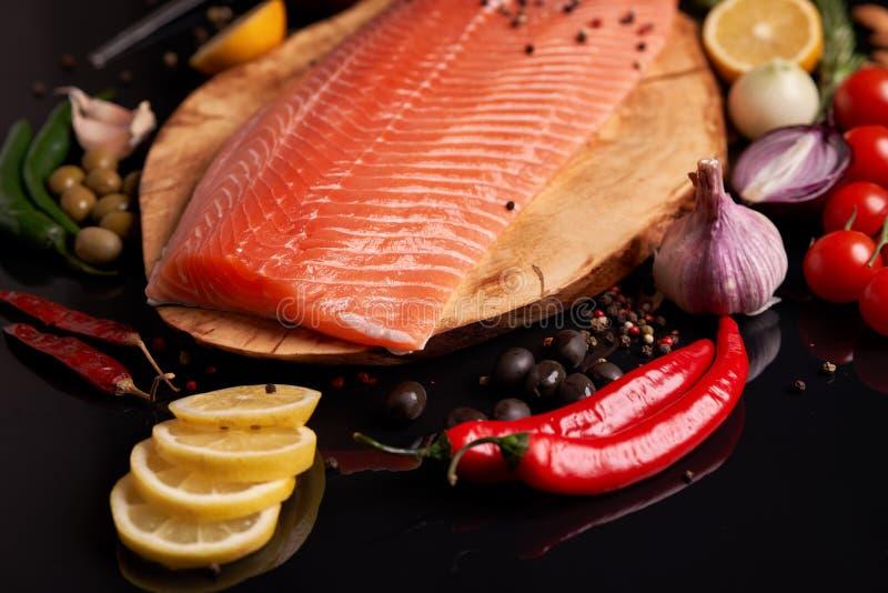 Hel r?d fiskfil? p? en tr?platta med k?rsb?rsr?da r?da och gr?na f?r chili f?r peppar, svarta och gr?na oliv f?r tomater, citron, royaltyfri bild