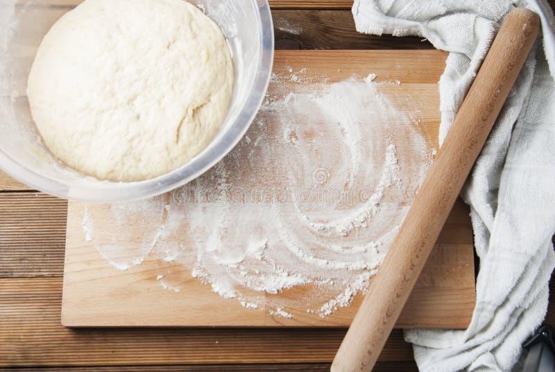 Hel vetepizza eller pajdeg som formas in i boll på pudrad träbakgrund casserole som lagar mat läckert home hemlagat recept royaltyfria foton